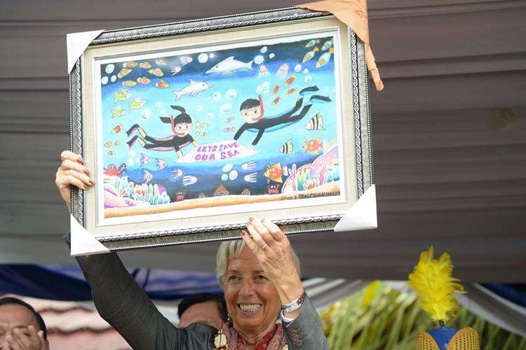Managing Director International Monetary Fund (IMF) Christine Lagarde menunjukkan sebuah gambar dengan pesan penyelamatan laut dalam kunjungannya di Cilincing, Jakarta, Rabu (28/2/2018). Lagarde menyambangi Jakarta untuk menghadiri konferensi internasional tingkat tinggi sekaligus persiapan untuk pertemuan tahunan IMF dan Kelompok Bank Dunia yang akan diselenggarakan di Nusa Dua, Bali, Oktober mendatang.