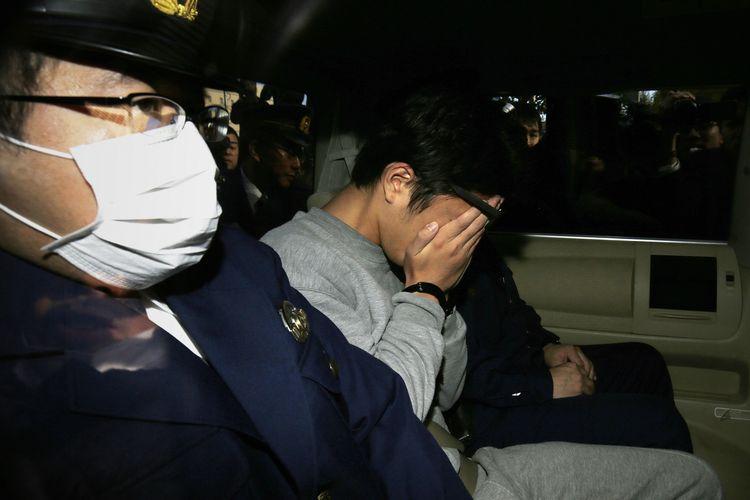 Takahiro Shiraishi (tengah) terdakwa pembunuhan 9 orang yang dijuluki Twitter Killer, menutupi wajahnya saat dibawa ke pengadilan dari kantor polisi Tokyo, Jepang, 1 November 2017.