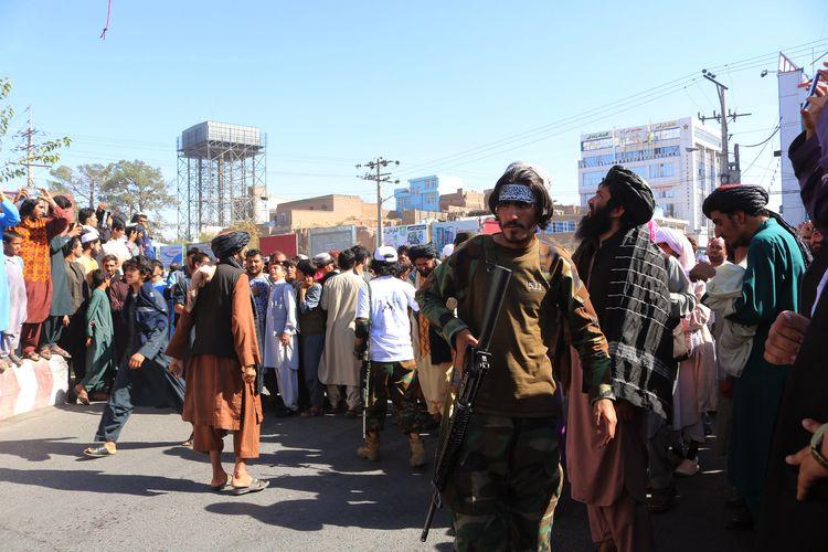 Orang-orang berkumpul di alun-alun kota Herat di barat Afghansitan, di mana Taliban menggantung mayat terduga penculik menggunakan crane pada Sabtu, 25 September 2021. Taliban mengumumkan jasad itu digantung sebagai peringatan jika ada yang hendak berbuat jahat.