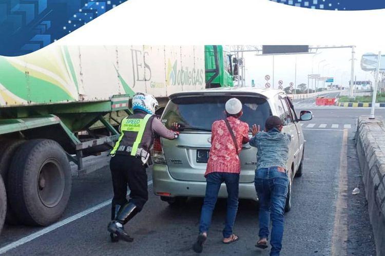 Bripka Bambang, anggota Satlantas Polres Gresik saat membantu mendorong mobil yang mogok di exit tol Kebomas, Minggu (1/11/2020).