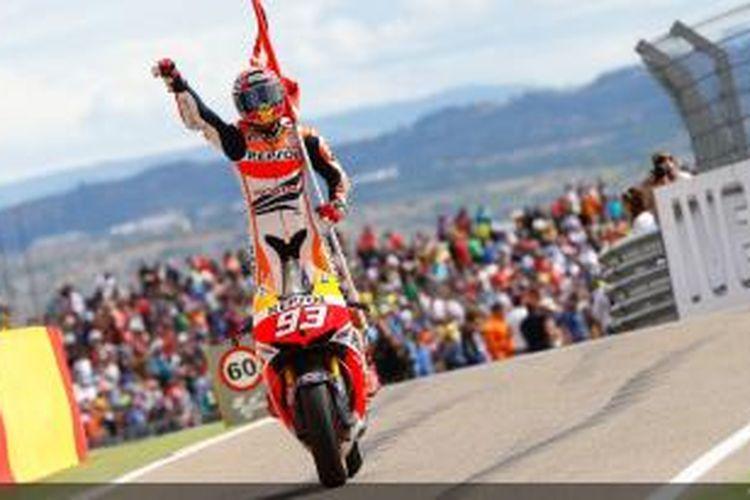 Pebalap Honda asal Spanyol, Marc Marquez, berdiri di atas motor merayakan kemenangannya di GP Aragon yang berlangsung di Sirkuit MotorLand Aragon, Minggu (29/9/2013).