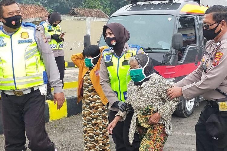 Seorang Polwan Polresta Tasikmalaya, ingin mengendong dan membantu berjalan kaki seorang nenek tua renta supaya dapat bantuan sembako saat pandemi corona di kawasan Gunung Galunggung, Tasikmalaya, Selasa (4/8/2020) kemarin.