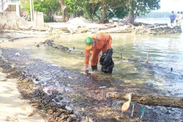 Petugas PPSU Kep Seribu mengumpulkan tumpahan minyak yang sudah berubah menjadi padat di pinggir pantai Pulau Pari, Kep. Seribu, Selasa (11/8/2020)