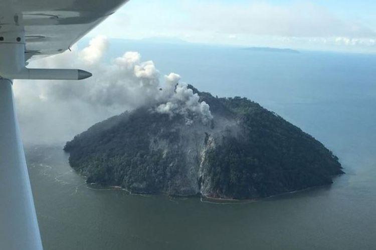 Gunung setinggi 500 meter yang diyakini tidak pernah meletus, memuntahkan asap tebal, di pulau kecil Kadovar, Papua Nugini, sejak Jumat (5/1/2018). (Samaritan Aviation via Facebook)