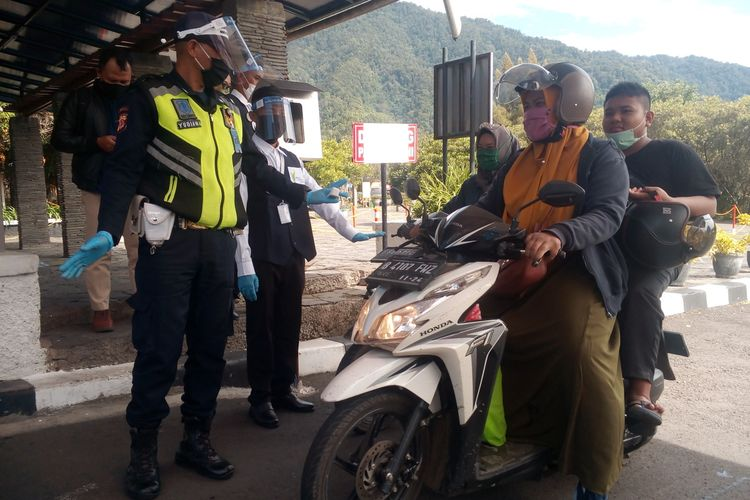 Petugas pintu masuk Kebun Raya Cibodas, Cianjur, Jawa Barat memeriksa pengunjung sebelum masuk ke area kebun raya, Selasa (7/7/2020). Pihak pengelola kembali membuka KRC untuk umum setelah ditutup sejak pandemi Covid-19