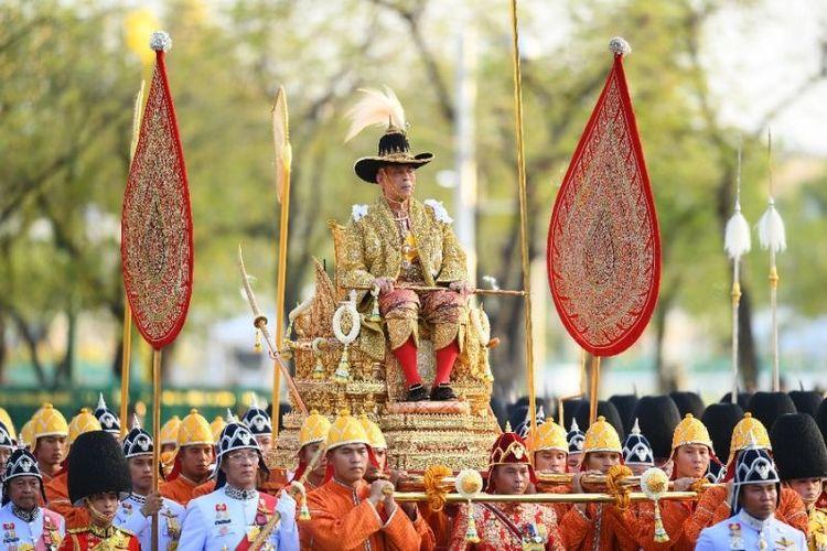 Raja Thailand Maha Vajiralongkorn dibawa melewati jalanan Bangkok dalam prosesi kerajaan hari kedua, Minggu (5/5/2019). (AFP/MANAN VATSYAYANA)