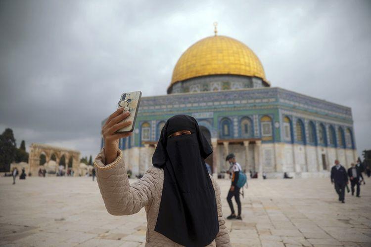 Seorang wanita Muslim mengambil foto selfie di samping Masjid Kubah Batu di kompleks Masjid Al Aqsa, Haram Asy-Syarif di kota tua Yerusalem, Jumat, 6 November 2020.