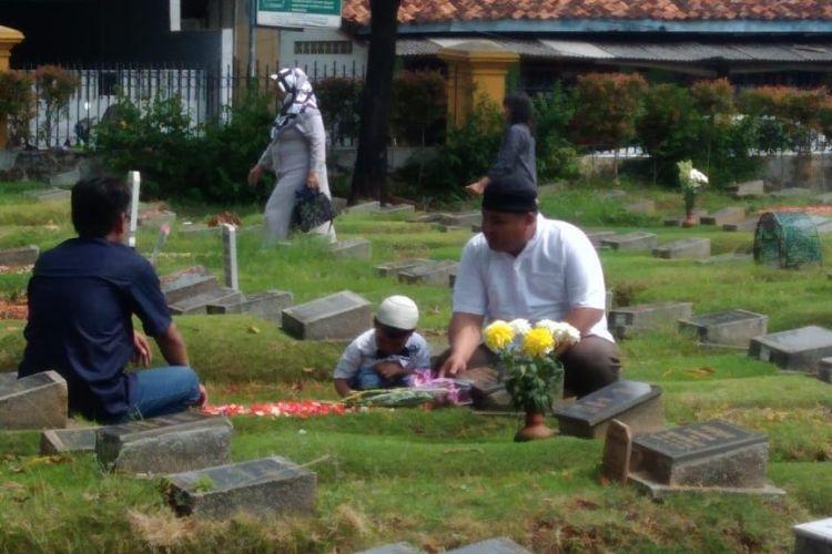 Ismet (kiri) bersama Amin dan anaknya (kanan) sedang melakukan ziarah kubur di Hari Pertama Lebaran di makam anggota keluarganya yang ada di TPU Jogol, Jumat (15/6/2018).