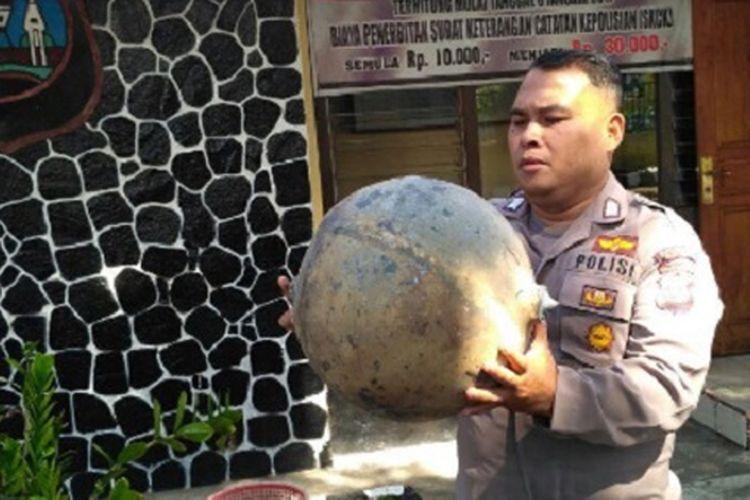 Seorang polisi di Polsek Tanjung Raya, Kabupaten Agam, Sumatera Barat, memegang benda yang jatuh dari udara, Selasa (18/7/2017).