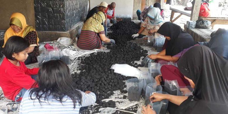 Sejumlah warga tengah merapikan briket batok kelapa setelah dicetak di Desa Sukapura, Kecamatan Rawamerta, Kabupaten Karawang, Rabu (2/9/2020).