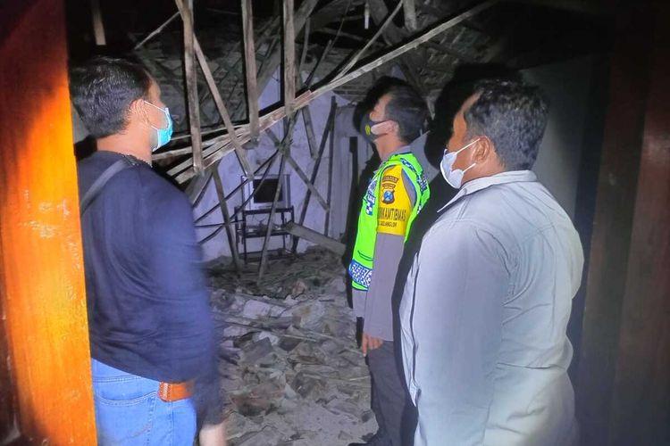 ROBOH-Polisi dan warga melihat kondisi atap rumah warga yang roboh saat penghuni didalamnya sementara nonton acara di televisi di Desa Prajegan, Kecamatan Sukorejo, Kabupaten Ponorogo, Jawa Timur, Kamis (24/9/2021) malam.