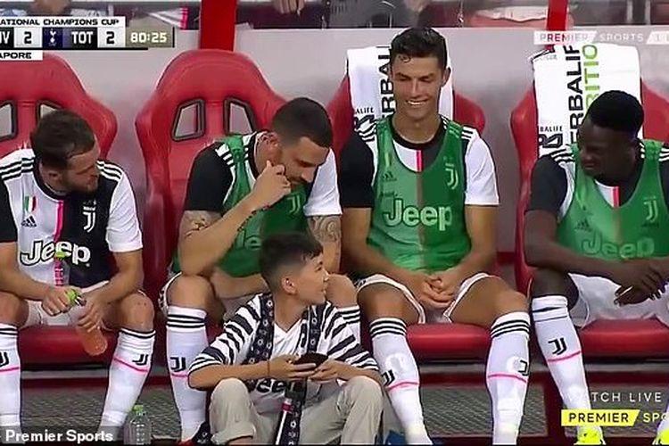 Cristiano Ronaldo saat mempersilahkan seorang anak untuk duduk di depan bangku cadangan Juventus di National Stadium, Singapura, Minggu (21/7/2019).