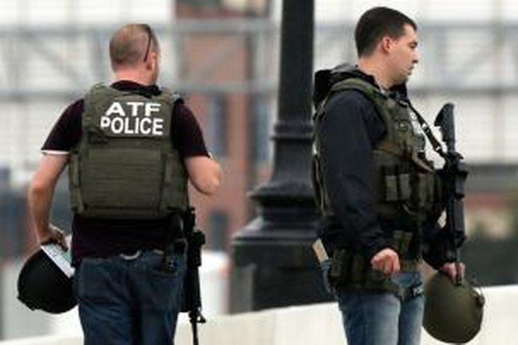 Para agen pemerintah bersiaga dengan senjata lengkap di sekitar Washington Navy Yard tempat penembakan yang dikhawatirkan menewaskan beberapa orang.
