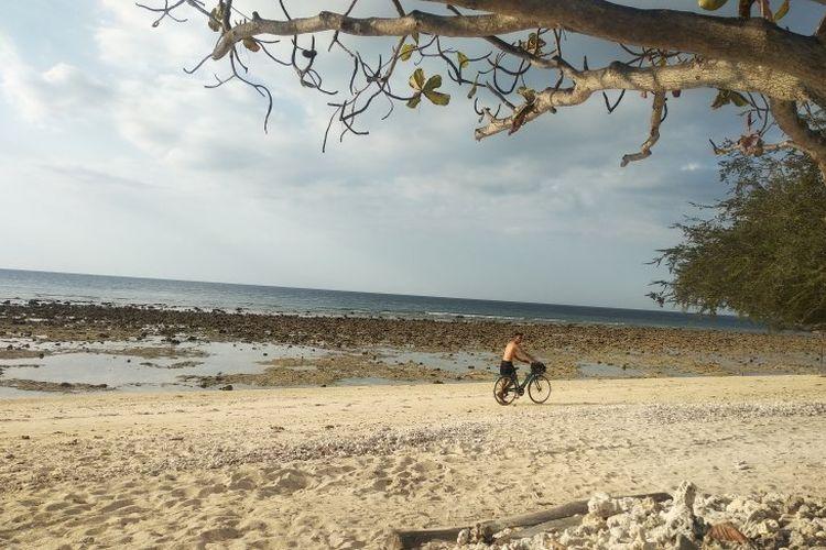 Seorang turis bersepeda di kawasan pantai Gili Trawangan, Lombok Utara, Nusa Tenggara Barat