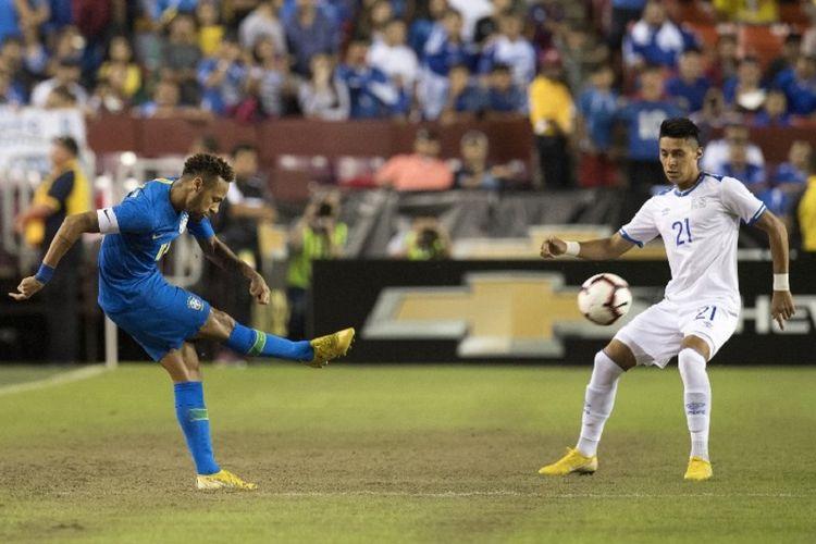 Penyerang asal Brasil, Neymar (kiri), menembak bola dalam penjagaan pemain El Salvador, Bryan Tamacas, pada pertandingan persahabatan, Rabu (12/9/2018).