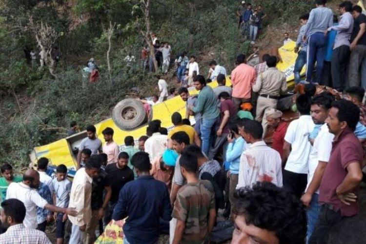 Warga melihat bangkai bus yang terjatuh ke dalam ngarai di Nurpur, negara bagian Himachal Pradesh, utara India, Senin (9/4/2018).