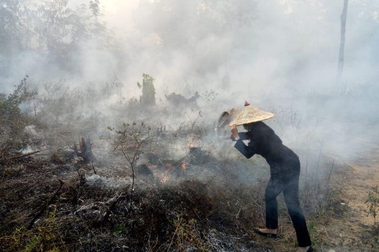 Bupati Kabupaten Landak, Karolin Margret Natasa saat berupaya memadamkan api yang membakar lahan di Kecamatan Mandor, Senin (20/8/2018)