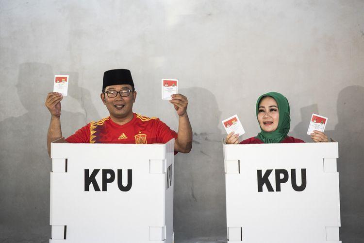Calon Gubernur Jawa Barat nomor urut satu Ridwan Kamil (kiri) bersama istri Atalia Praratya (kanan) menunjukkan surat suara saat menggunakan hak pilih di TPS 21 Bandung, Jawa Barat, Rabu (27/6/2018). Pilgub Jabar diikuti empat pasang cagub dan cawagub dengan jumlah daftar pemilih tetap (DPT) sebanyak 31.735.133 pemilih.