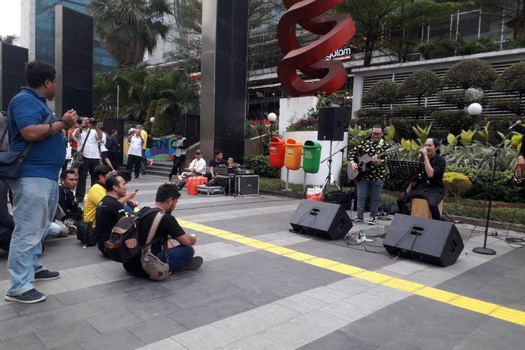 Warga lesehan menikmati pertunjukan musik di trotoar sudirman, Rabu (29/8/2018)