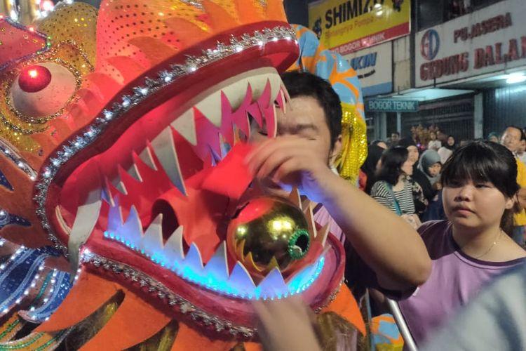 Pengunjung memasukkan angpao ke dalam mulut Liong di acara Bogor Street Festival Cap Go Meh 2020, Sabtu (8/2/2020).