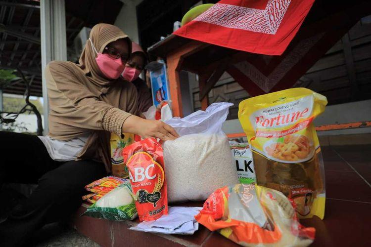 BANTUAN— Wiwik Endarini pemilik warung di RT 24, Kelurahan Madiun Lor, Kecamatan Manguharjo, Kota Madiun menunjukkan bantuan bahan makanan yang diberikan Pemkot Madiun untuk dimasak menjadi makanan yang bergizi bagi warga isoman dilingkungannya.