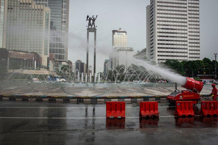 Petugas Damkar menyemprotkan cairan disinfektan di kawasan Bundaran HI, Jakarta, Minggu (22/3/2020). Pemprov DKI Jakarta melakukan penyemprotan fasilitas umum menggunakan cairan disinfektan di lima wilayah DKI Jakarta untuk mencegah penyebaran virus Corona atau COVID-19.