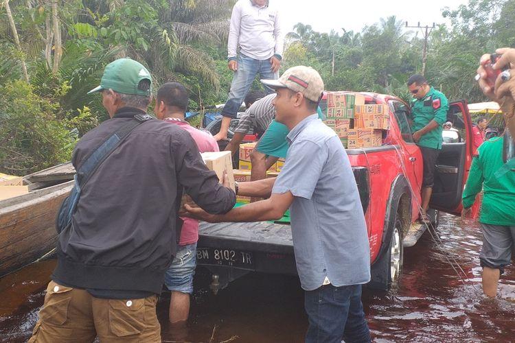 Proses penyaluran bantuan 1 ton beras dan 300 kardus indomie dari PWNU Riau untuk korban banjir di Desa Buluh Cina, Kecamatan Siak Hulu, Kabupaten Kampar, Riau, Rabu (25/12/2019). Penyaluran bantuan menggunakan dua unit perahu mesin menuju kantor desa.