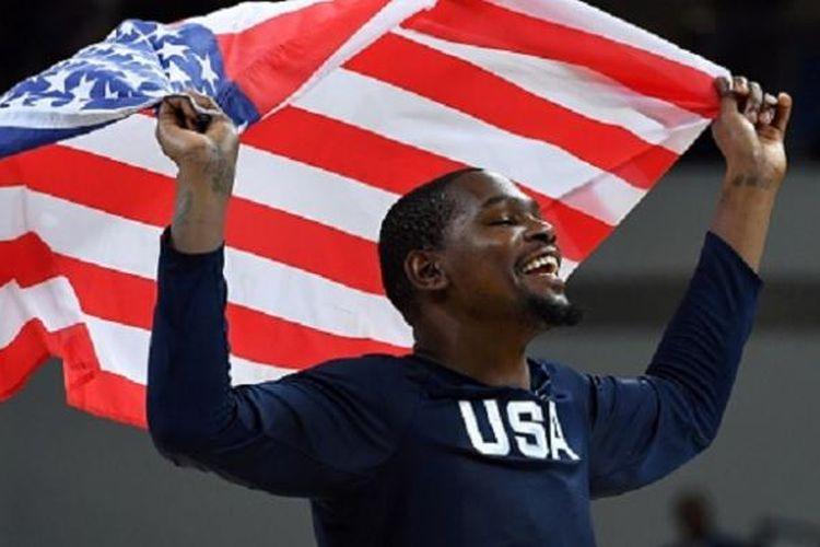 Kevin Durant mengibarkan bendera Amerika Serikat seusai timnya memenangi medali emas pada final versus Serbia, Minggu (21/8/2016).