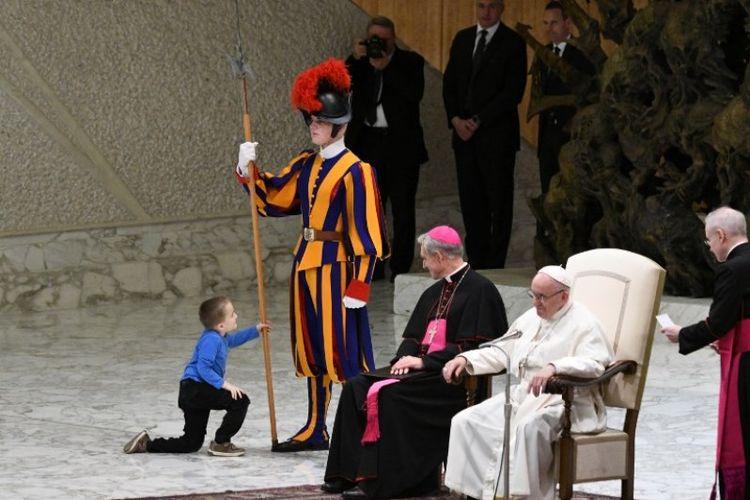 Seorang anak lelaki naik atas panggung bermain dengan tombak Pasukan Swiss saat Paus Franci smelakukan audiensi umum mingguan pada Rabu (28/11/2018) di aula Paul VI di Vatikan. (AFP/Vincenzo Pinto)
