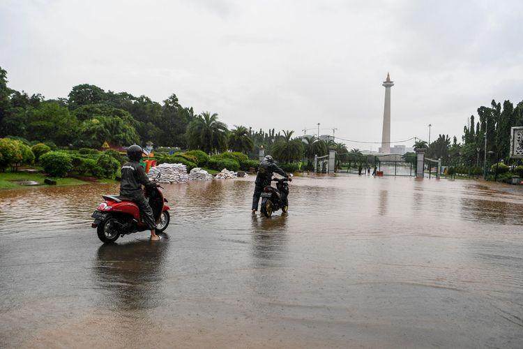 Warga mendorong motor melintasi banjir di kawasan Monas, Jalan Medan Merdeka Barat, Jakarta, Minggu (2/2/2020). Hujan deras yang mengguyur Jakarta pada Minggu (2/2/2020) pagi menyebabkan beberapa ruas jalan di ibu kota tergenang banjir dengan ketinggian 10-50 sentimeter.