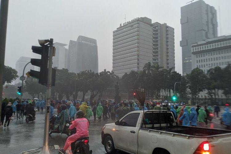 Massa aksi menolak Undang-Undang Cipta Kerja berlarian membubarkan diri ke arah Jalan Medan Merdeka Selatan setelah hujan lebat mengguyur lokasi aksi di Patung Kuda Jakarta Pusat, Jumat (16/10/2020), Jumat (1