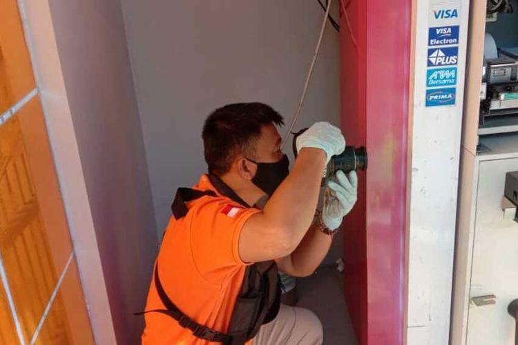 Kepala Unit Inafis Satreskrim Polresta Tasikmalaya, Dede Nurjalil memeriksa lokasi pembobolan ATM secara teliti di lokasi kejadian Jalan Galunggung Kota Tasikmalaya, Kamis (25/3/2021).