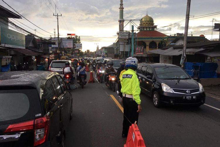 Petugas kepolisian tampak sedang mengatur arus lalu lintas di Jalan Raya Puncak Bogor arah Jakarta pada sore hari, Senin (25/5/2020).