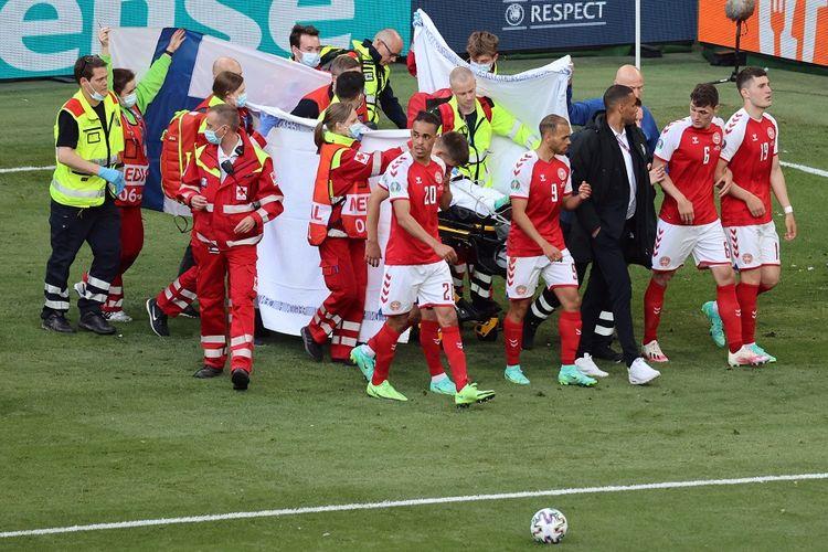Para pemain Denmark saling menjaga saat paramedis merawat gelandang Christian Eriksen (tidak terlihat) dalam laga Grup B UEFA Euro 2020 antara Denmark dan Finlandia di Stadion Parken di Kopenhagen pada 12 Juni 2021.