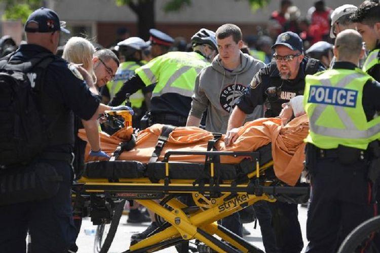 Paramedis bergegas membawa korban luka dalam insiden penembakan di Toronto, Kanada, Senin (17/6/2019). Saat insiden, warga tengah merayakan gelar juara klub basket NBA Toronto Raptors.
