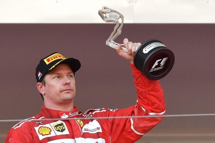 Pebalap Scuderia Ferrari, Kimi Raikkonen, mengangkat paial setelah finis di urutan kedua pada balapan GP Monaco di Sirkuit Monaco, Monte Carlo, Minggu (28/5/2017).
