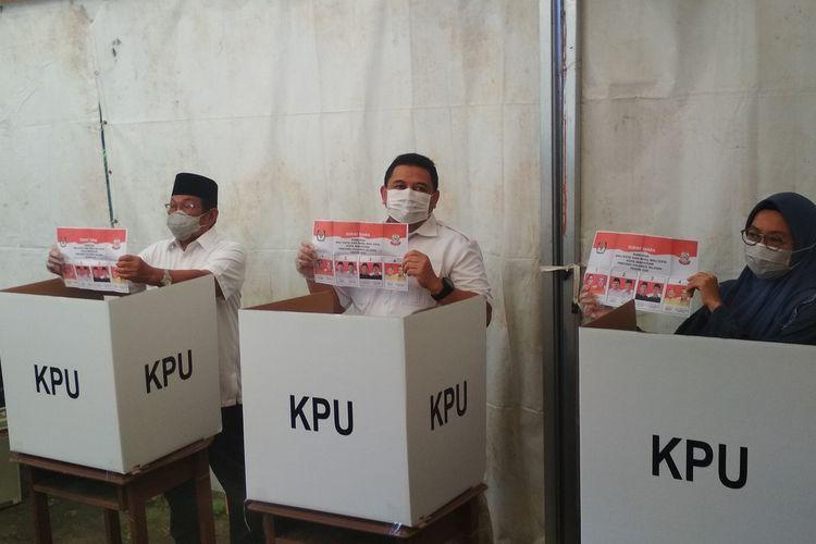 Calon Wali Kota Makassar nomor urut 2 Munafri Arifuddin (tengah) saat mencoblos bersama Aksa Mahmud (kiri) dab istrinya Melinda Aksa di Kelurahan Sawerigading, Kecamatan Ujung Pandang, Makassar, Rabu (9/12/2020).