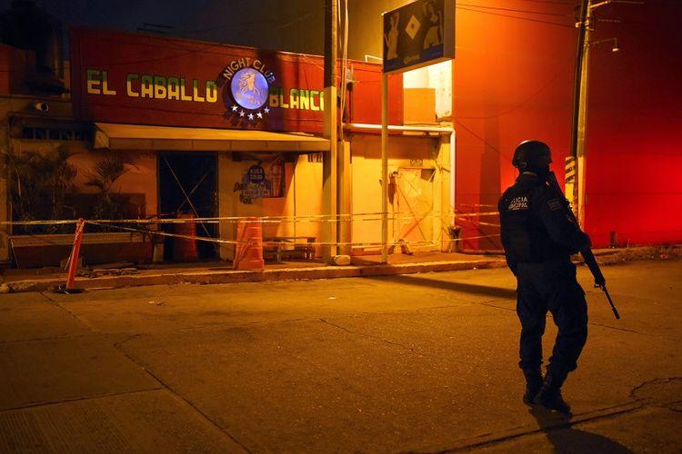 Polisi bersenjata berjaga di luar bar dan klub penari telanjang Caballo Blanco yang menjadi sasaran penyerangan dan pembakaran di kota Coatzacoalcos, negara bagian Veracruz, pada Selasa (28/8/2019) malam.