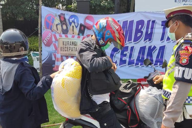 Kepolisian saat menyekat salah satu pengendara motor yang hendak mudik di posko penyekatan yang berada di Jalan Gatot Subroto, Jatiuwung, Kota Tangerang, pada hari keempat larangan mudik Lebaran 2021, Minggu (9/5/2021).