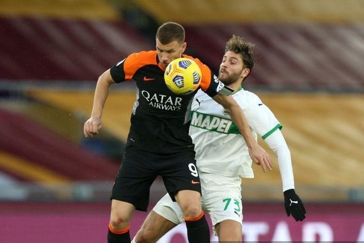 Striker AS Roma, Edin Dzeko, dikawal oleh pemain Sassuolo Jeremie Boga dalam laga AS Roma vs Sassuolo, Minggu (6/12/2020).