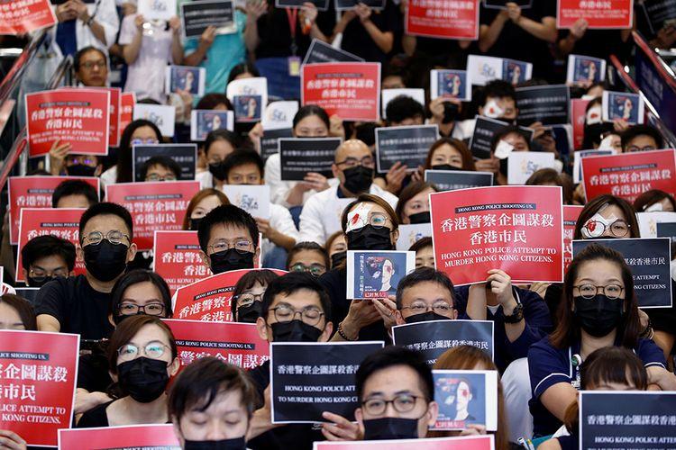 Staf medis membawa spanduk saat aksi mogok mengutuk kekejaman polisi saat terjadi protes anti-pemerintah baru-baru ini, di Rumah Sakit Queen Elizabeth di Hong Kong, China, Selasa (13/8/2019). Demo Hong Kong berlangsung intens dalam dua bulan terakhir dan berujung ricuh sejak UU Ekstradisi yang kontroversial mulai mendapat penolakan dari masyarakat.