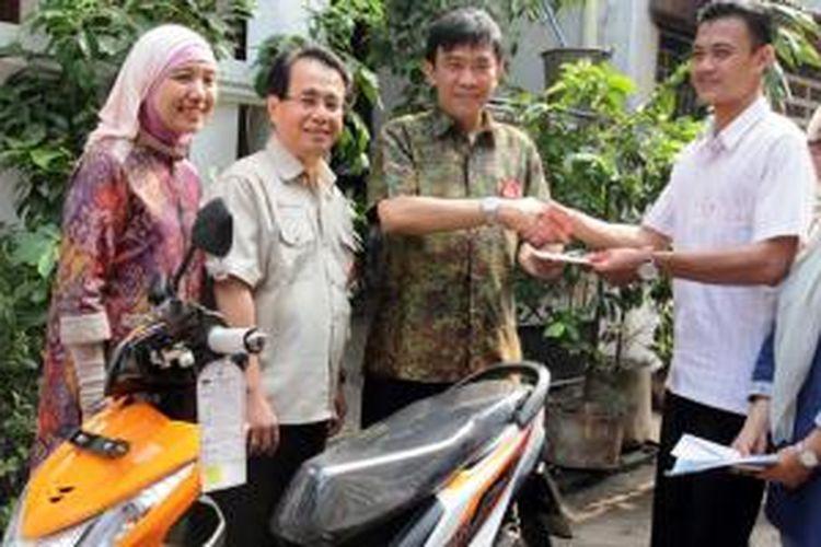 Margono Tanuwijaya menyerahkan sepeda motor pesanan konsumen langsung ke tangan pelanggan di rumahnya, di dampingi Sigit Kumala dan Istiyani Susriyati.