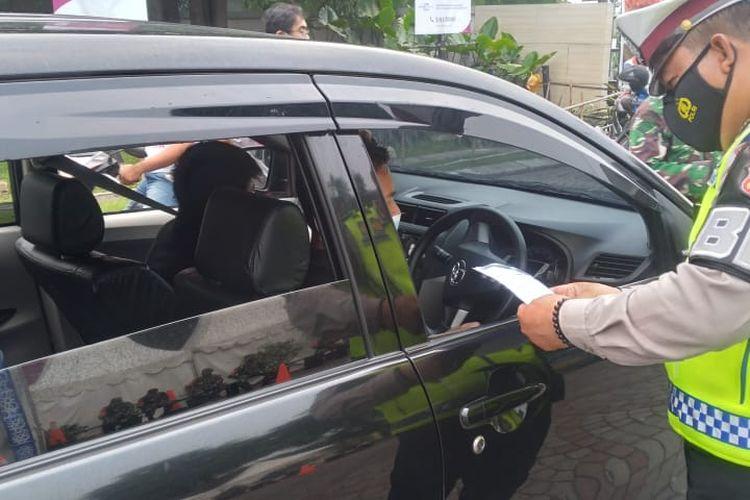 Kepolisian saat memeriksa dokumen-dokumen dari pengendara yang hendak melintas posko penyekatan di Jalan Gatot Subroto, Jatiuwung, Kota Tangerang, Kamis (6/5/2021).