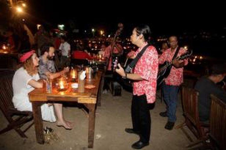 Grup musik menghibur turis asing saat makan malam di pinggir pantai Jimbaran, Bali, Jumat (21/6/2013). Kawasan Jimbaran merupakan salah satu tempat tujuan wisatawan selama berlibur di Bali, sejumlah tempat wisata seperti Jimbaran fish market dan Pura Uluwatu berada dekat dengan kawasan ini.