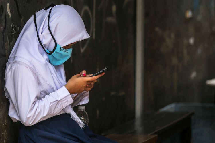 Sejumlah pelajar saat istirahat sejenak di luar Balai Warga RT 05/RW 02 Kelurahan Galur, Johar Baru, Jakarta Pusat, Selasa (1/9/2020). JAK Wifi adalah program internet gratis dari Pemprov DKI Jakarta yang ditujukan untuk pelajar di permukiman padat penduduk yang kesulitan mengakses internet.