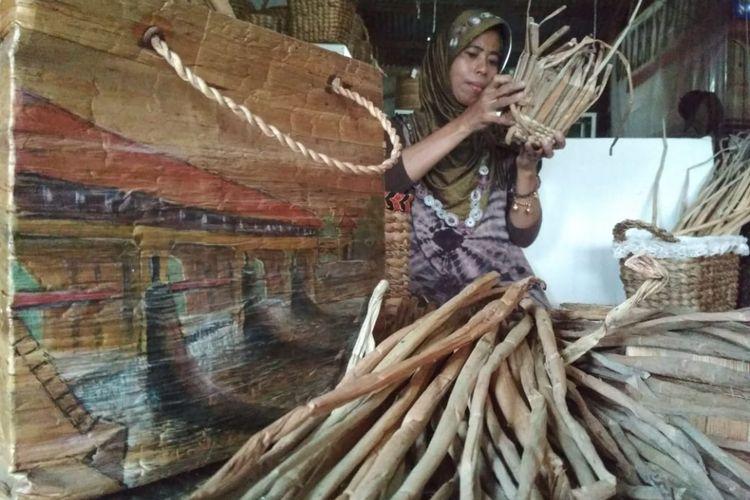 Sambinah (42) tengah menganyam vas bunga yang terbuat dari eceng gondok, Jumat (11/1/2019).Di tangan Sambinah (42), eceng gondok yang kerap dianggap sampah disulap menjadi produk bernilai ekonomis.