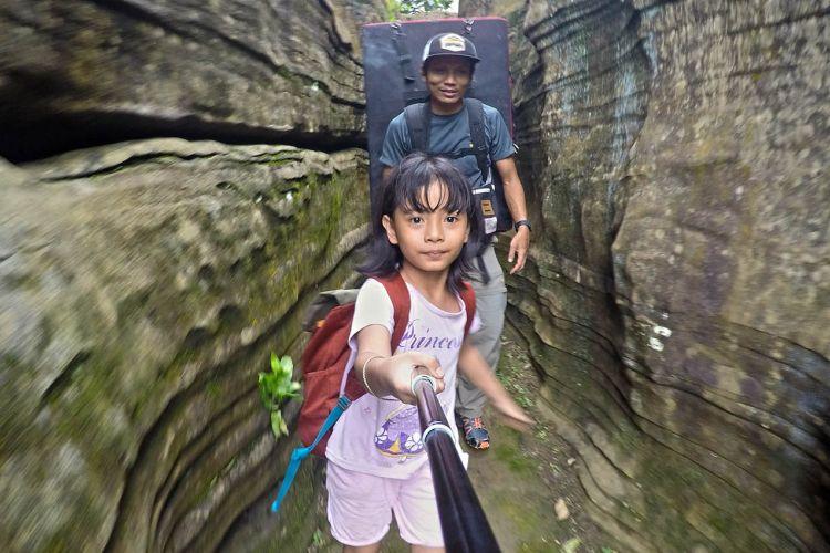 Bening, 8 tahun, trekking melintasi tebing karst di kawasan Gua Harunggang, di Babakan Madang, Kabupaten Bogor, Minggu (25/2/2018).