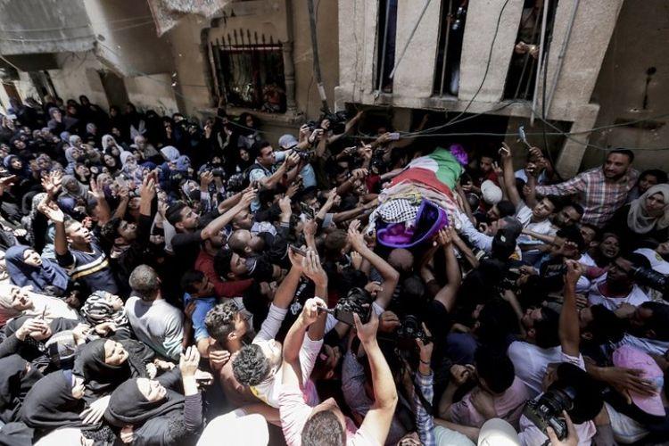 Para pelayat di Palestina mengangkat jenazah Razan Al Najjar (21) yang tewas ditembak mati oleh tentara Israel, di Khan Yunis pada Jumat (2/6/2018). (AFP/Mahmud Hams)