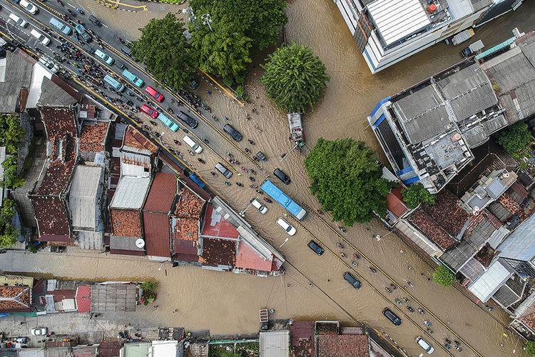 Foto aerial kendaraan melintasi banjir di Jalan Jatinegara Barat, Kampung Pulo, Jakarta, Senin (8/2/2021). Tingginya intensitas hujan mengakibatkan sejumlah wilayah di ibu kota terendam banjir.