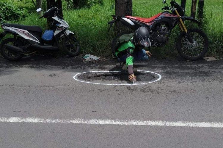 Driver gojek saat memberi tanda jalan berlubang di Jember agar pengendara terhindar dari kecelakaan